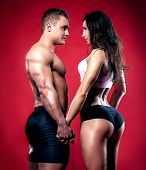 stock photo of nude couple  - Portrait of handsome athletic couple over red background - JPG