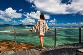 pic of jetties  - Woman with sarong on a tropical beach jetty at at Seychelles - JPG