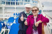 image of passenger ship  - Happy Senior Couple With A Thumbs Up On The Deck of A Luxury Passenger Cruise Ship - JPG