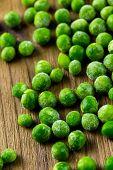 stock photo of sweet pea  - Organic frozen baby sweet peas on wood board. ** Note: Shallow depth of field - JPG