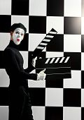 stock photo of clapper board  - Movie actor and a mime posing with clapper board with different emotions - JPG