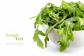 picture of rocket salad  - rucola or arugula fresh green rocket salad leaves eruca sativa in a white ceramic bowl isolated over the white background with copy space for your text - JPG