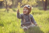 picture of knitwear  - Cute baby in knitwears playing at the garden - JPG