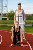 pic of competing  - Young sport couple in starting position prepared to compete and run - JPG