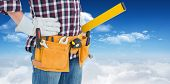 stock photo of hand tools  - Repairman wearing tool belt while standing with hands on hips against bright blue sky with clouds - JPG