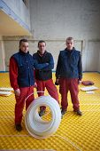 foto of convection  - grouo of workera installing underfloor heating and colling in modern home - JPG