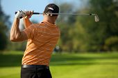 picture of swings  - Young man swinging golf club - JPG