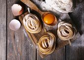 foto of pasta  - Raw homemade pasta and ingredients for pasta on wooden background - JPG