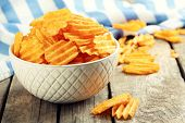 stock photo of potato chips  - Delicious potato chips in bowl on wooden table close - JPG