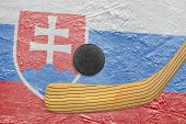 stock photo of hockey arena  - Hockey puck hockey stick and the image of the Slovak flag on ice - JPG