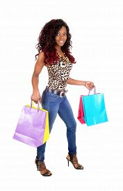 picture of sling bag  - A lovely sling young African American woman holding her colorful shopping bags bags smiling standing isolated for white background - JPG