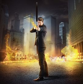 stock photo of bow arrow  - Businessman with bow and arrow on fire - JPG