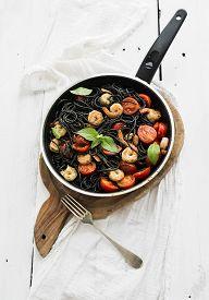 stock photo of black-cherry  - Black pasta spaghetti with shrimps - JPG