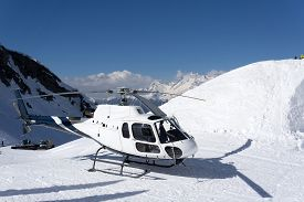 pic of helicopters  - White rescue helicopter parked in the snowy mountains - JPG