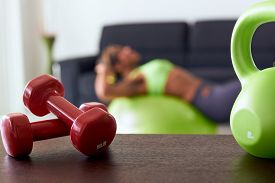 pic of abdominal  - Young adult african american woman in sports clothing at home doing domestic fitness and training abdominals on swiss ball in living room - JPG