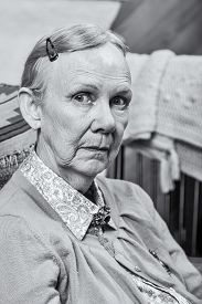 stock photo of matron  - Old woman seated and looking at camera - JPG