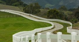 image of long winding road  - Country road with long white picket fence - JPG