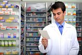 Pharmacist Reading Prescription At Pharmacy