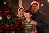 image of nuclear family  - Happy family portrait parents with young boy smiling at christmas tree - JPG