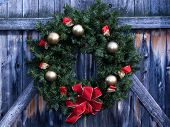 stock photo of christmas wreaths  - christmas wreath with gold balls gold ribbon red felt ribbon and red felt bow displayed on a rustic wooden fence gate - JPG