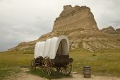 image of covered wagon  - An old covered wagon and a rock formation - JPG