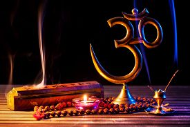picture of om  - Om symbol incense smoke candle and japa mala on wooden table at black background - JPG