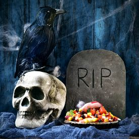 stock photo of amputation  - a plate with Halloween candies and an amputated finger in a dismal scene with a crow - JPG