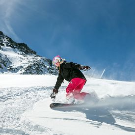 stock photo of snowboarding  - Young woman snowboarder in motion on snowboard in mountains - JPG
