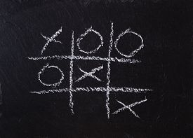 foto of tic  - Game Tic Tac Toe on black slate board - JPG