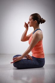 stock photo of pranayama  - Beautiful sporty fit yogini woman practices pranayama breath control exercise in yoga asana Padmasana  - JPG