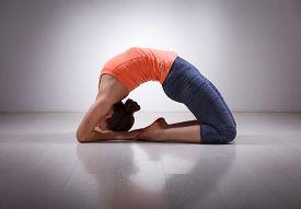 stock photo of ashtanga vinyasa yoga  - Beautiful sporty fit yogini woman practices yoga asana Kapotasana  - JPG