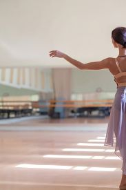 stock photo of ballet barre  - The classic ballet dancer posing at ballet barre on a rehearsal room background - JPG