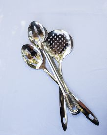 stock photo of chafing  - serving spoons for a buffet sitting on top of eachother - JPG