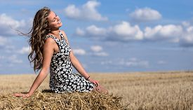 image of haystacks  - Full length portrait of young adult girl on haystack against blue sky with clouds and autumn field wear white sweater - JPG