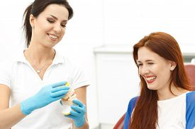 stock photo of false teeth  - Dentist holding false teeth with patient in clinic - JPG