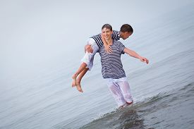 stock photo of squirt  - Two merry happy brother plays at sea laughing and squirting water italy - JPG
