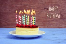 image of yesteryear  - the text happy birthday and a cheesecake with some lighted birthday candles of different colors - JPG