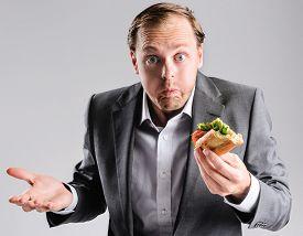image of takeaway  - Busy businessman eating takeaway sandwich on the go - JPG