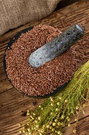 stock photo of flax seed oil  - Vertical photo with stone marble mortar bowl full of flax seeds placed on wooden board with burlap in background - JPG