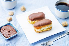 image of eclairs  - eclairs with cheese cream and chocolate glaze on a blue background - JPG