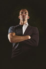 picture of half-dressed  - Confident rugby player with arms crossed against half a suit - JPG