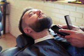 stock photo of barber razor  - barber shaving beard with electric razor and holding comb in barbershop - JPG