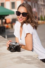 picture of analogy  - Gorgeous young brunette woman using analog camera - JPG