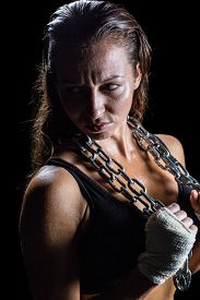 picture of annoying  - Annoyed female athlete holding chain against black background - JPG