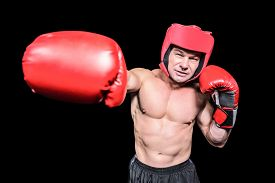 stock photo of headgear  - Boxer with red headgear punching against black background - JPG