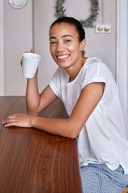 foto of pyjama  - portrait of smiling young black mix race woman at home in pyjamas with coffee cup - JPG