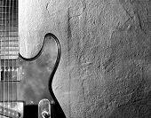 Schwarz / weiß Foto einer Elertric-Gitarre in der Nähe von Wand