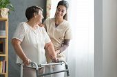Nurse Helping Senior To Walk poster