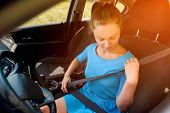 Stylish Girl In Dress In Car Seat Belt For Safety Before Driving. Beautiful Young Woman In Car Faste poster