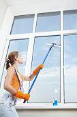 The girl in gloves washing windows mop for washing windows